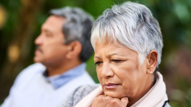 Shot of a senior woman of color looking upset with her husband in the background