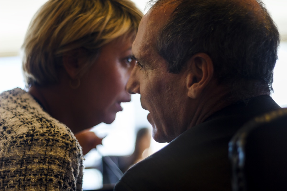 Businesswoman whispering to her colleague around a conference table