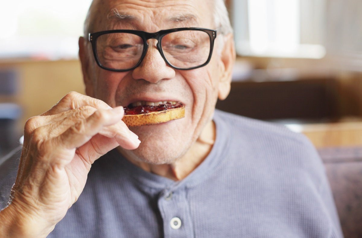 A senior man enjoys a bite of his toasted bread spread with sweet jelly jam preserves during breakfast at a restaurant.