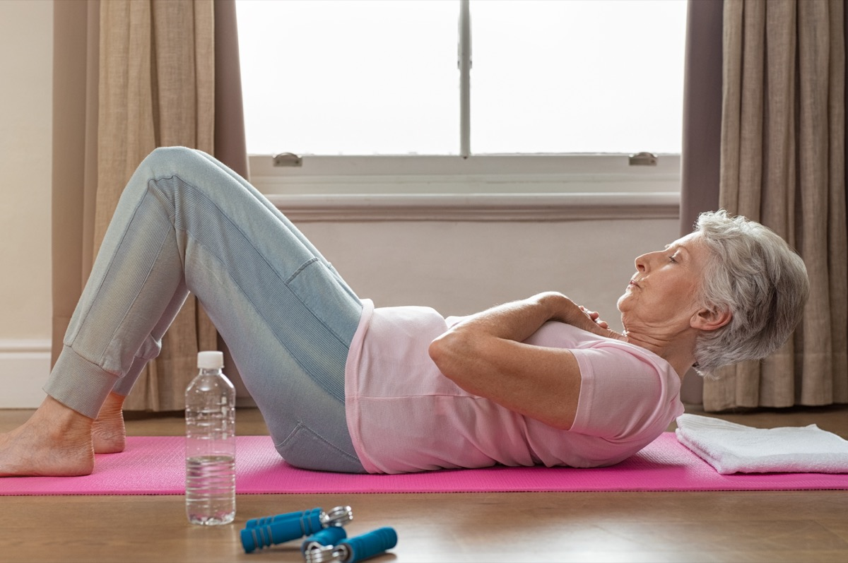 senior woman on yoga mat, crosses arms in preparation for crunches