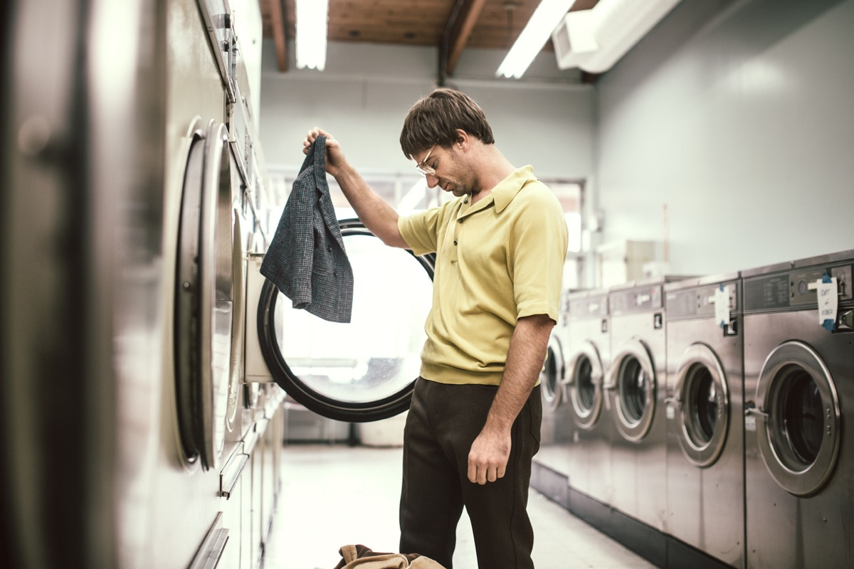 A man in 1980's style does his laundry at an old school laundromat. He holds up his jacket which has shrunken to a ridiculously small size while drying in the dryer, his head hanging down in sadness and disappointment.