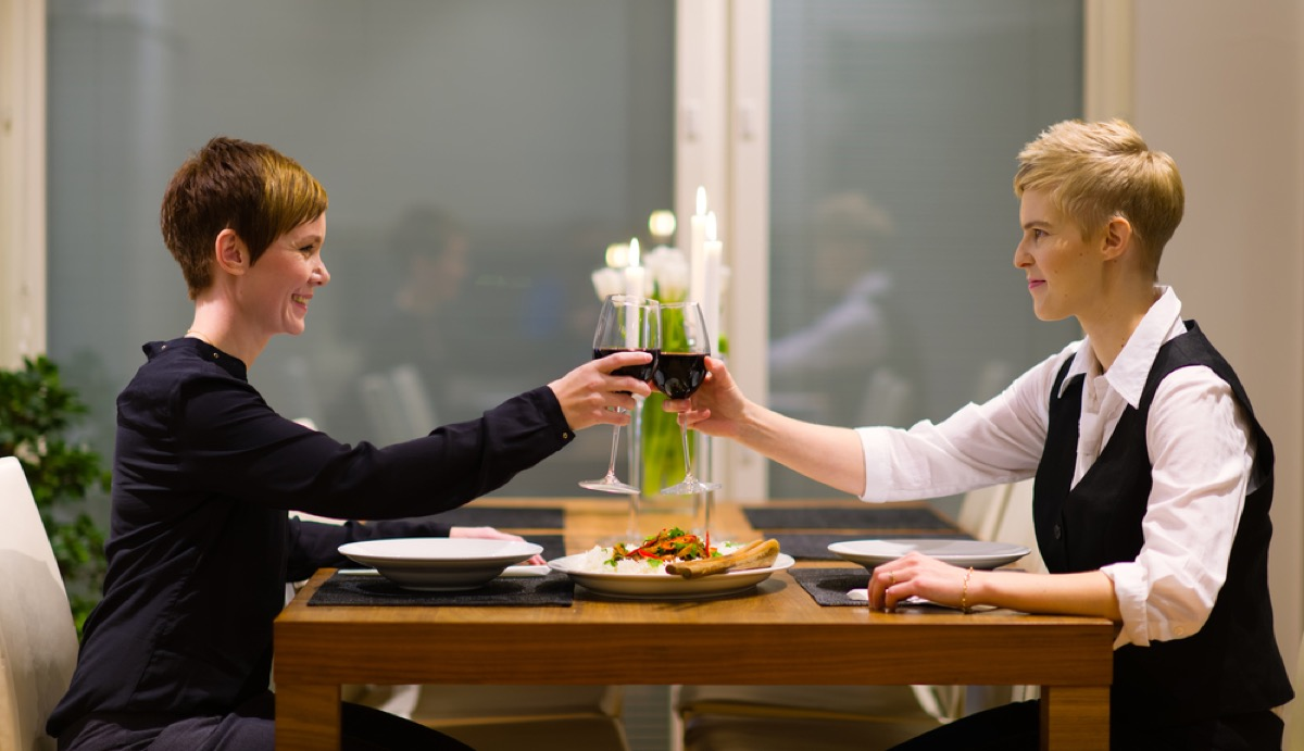 two white women toasting red wine over meal at home