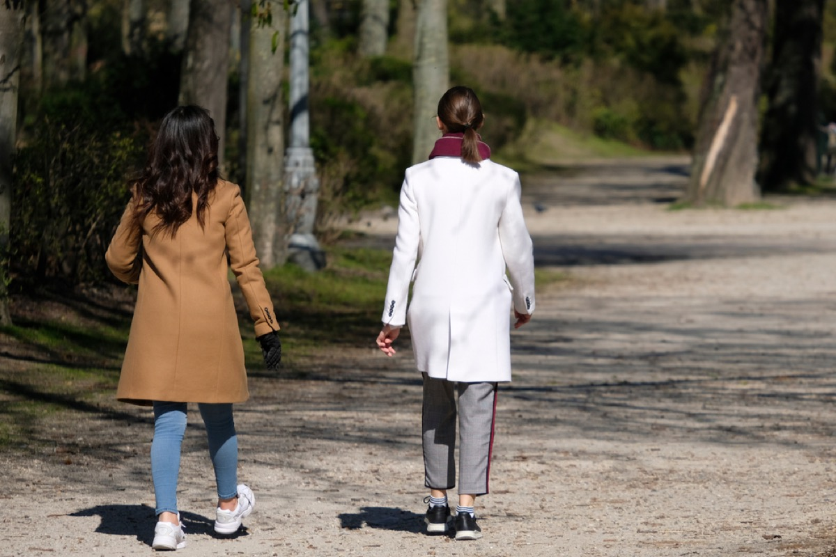 two women walking on a path from behind