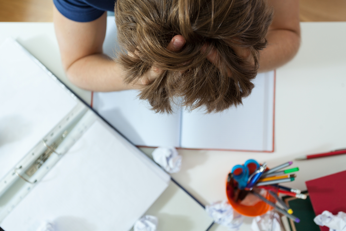 gender neutral person has head in hands while doing homework