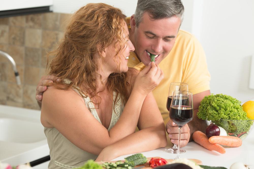 white woman feeding vegetable to white man with wine