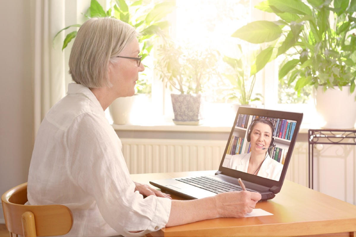 older white woman video chatting with doctor on laptop