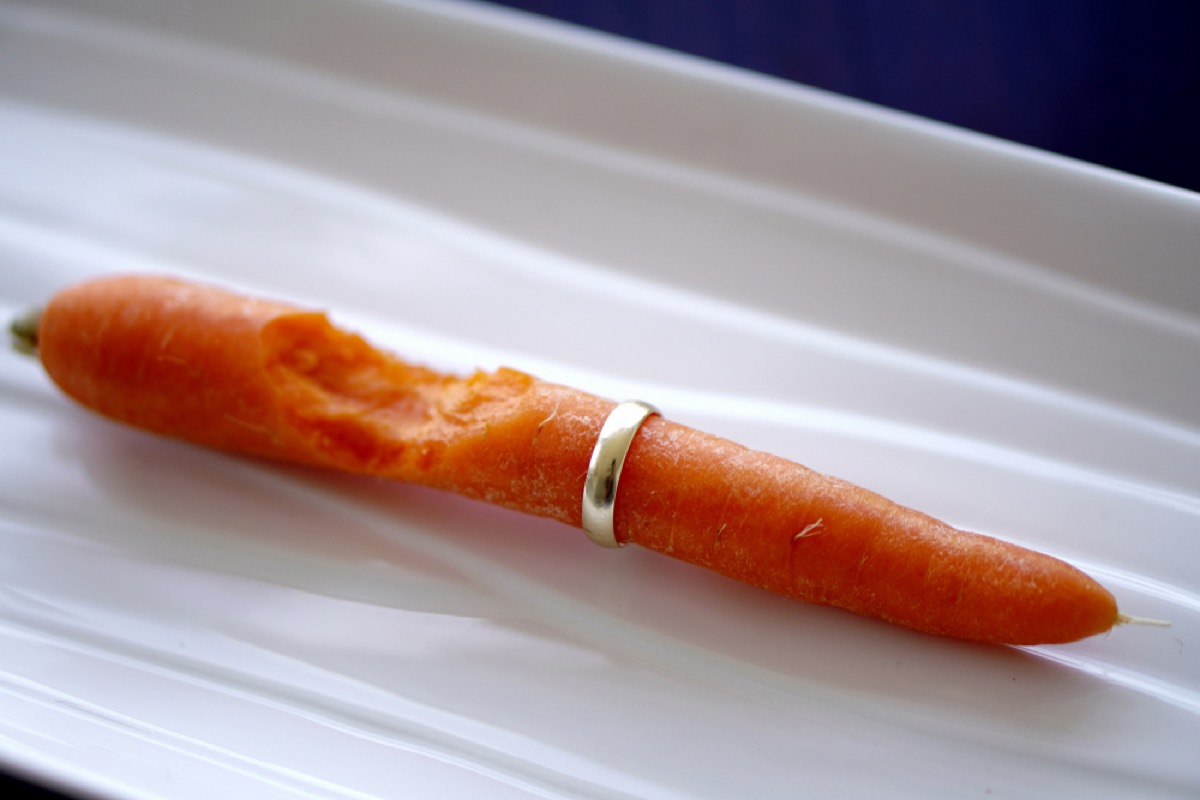 A carrot with a gold ring on it and a bite taken out of the carrot