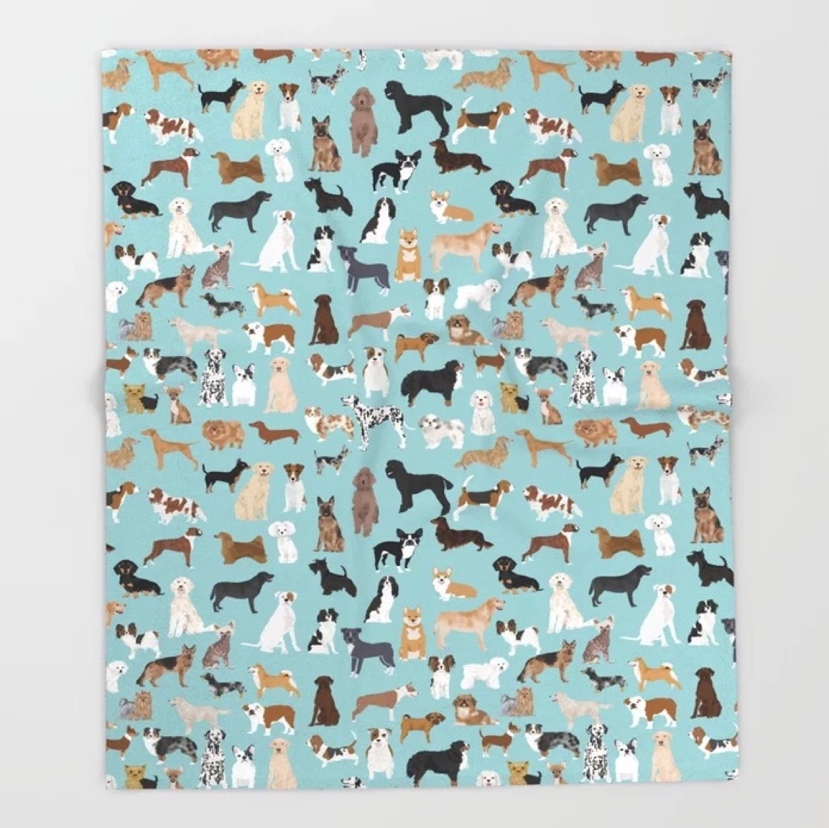 A blue throw blanket with dogs all over it