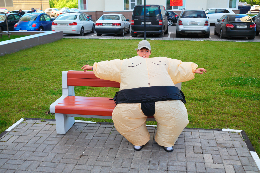 boy wears sumo wrestler inflatable fat suit halloween costume while sitting on bench