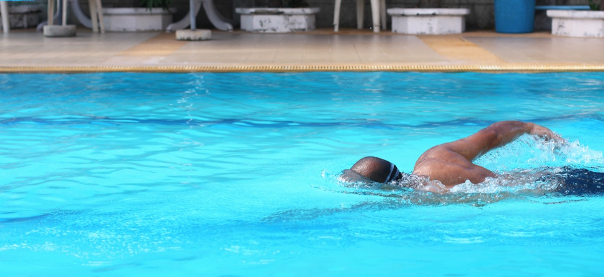 Black man swimming laps outdoors at the pool