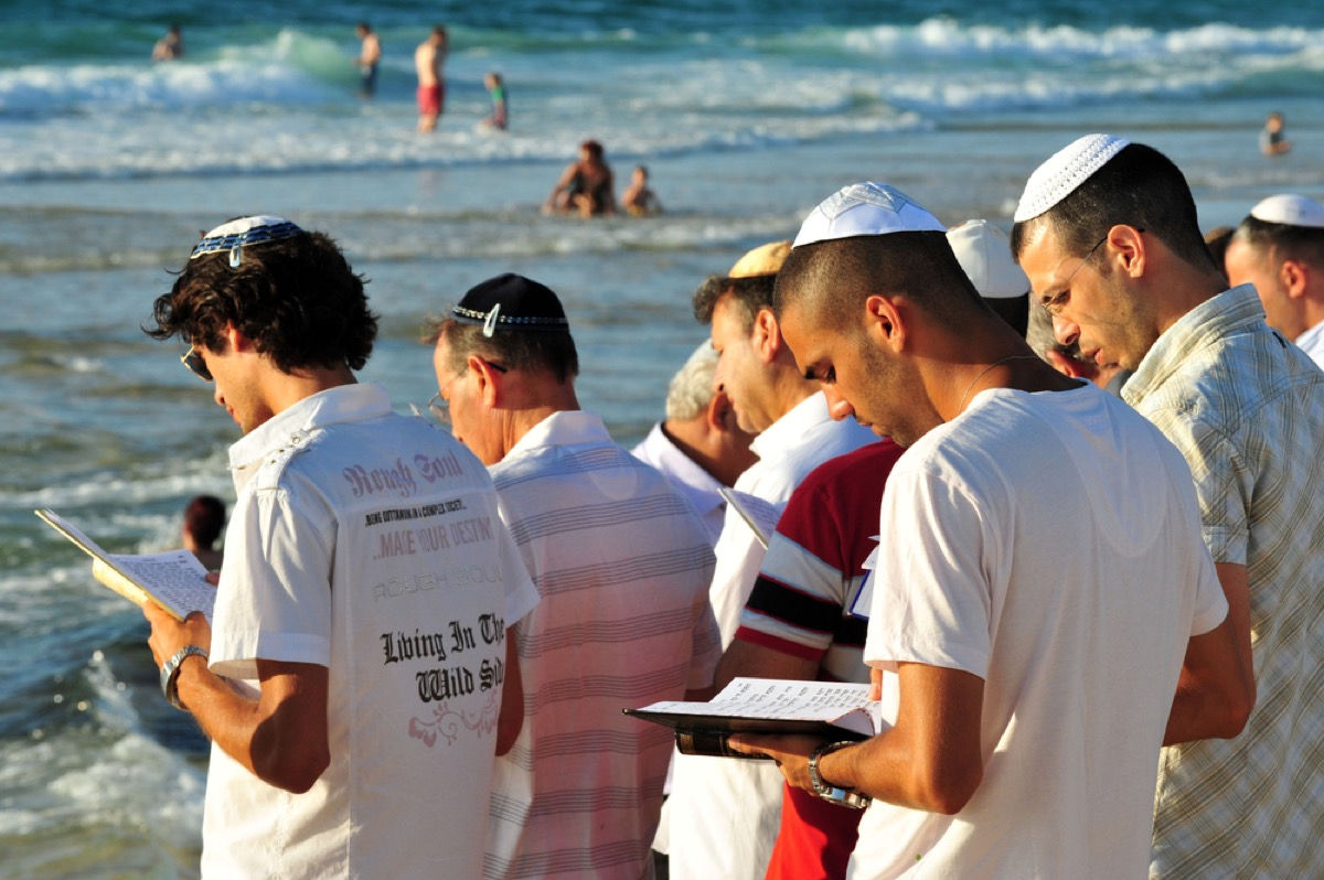 jewish men at the edge of a body of water reading torah, rosh hashanah facts