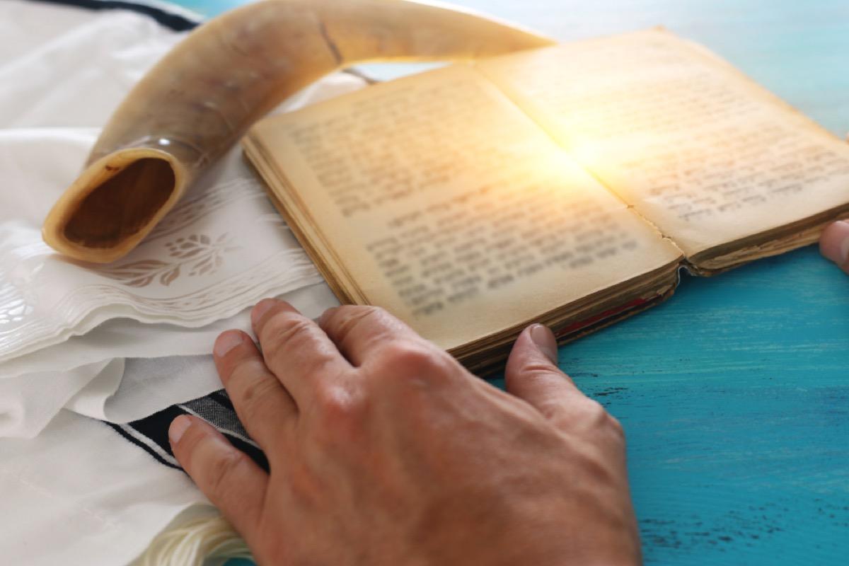 man reading torah with tallit and shofar behind it