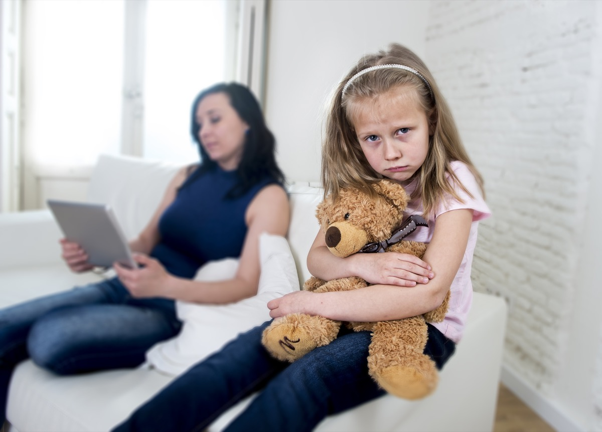 unhappy child sitting on couch while her mother is on her ipad