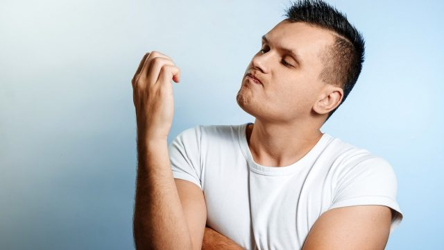Portrait of a man on a light background, looking at his nails.