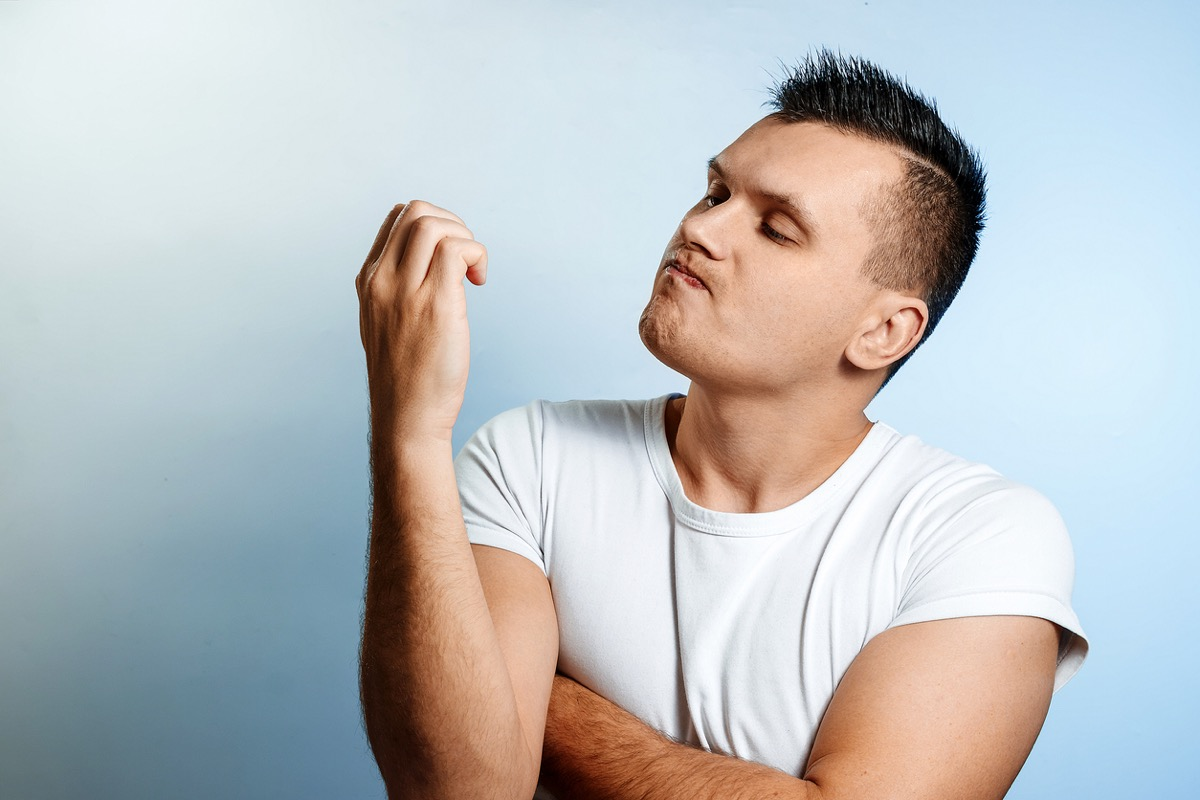Portrait of a white man on a light background, looking at his nails.