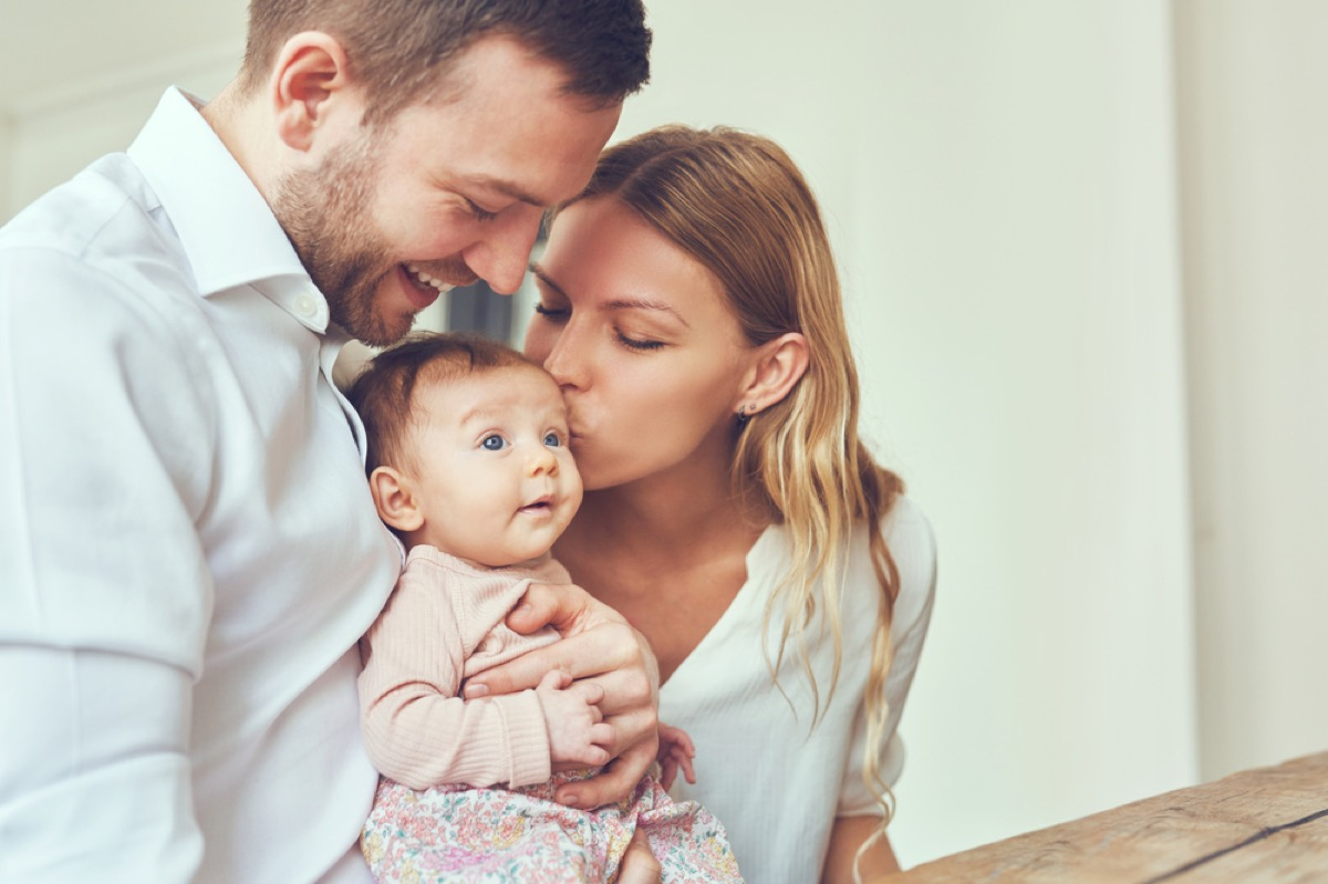 white mother and father holding and kissing newborn baby girl