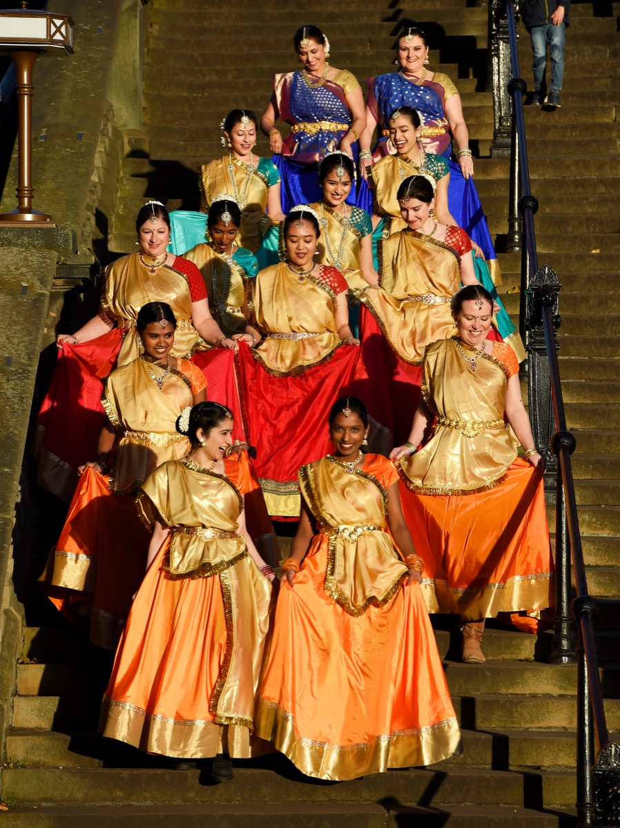 a group of women dressed in traditional indian garb on steps