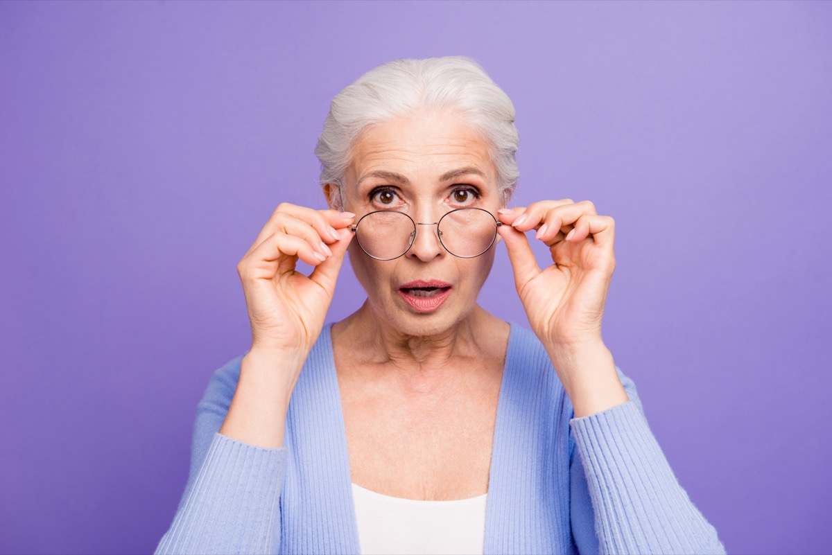 Portrait of beautiful nice amazed gray-haired old lady wearing casual and glasses, showing gesture, putting spectacles down. Isolated over pastel violet purple background
