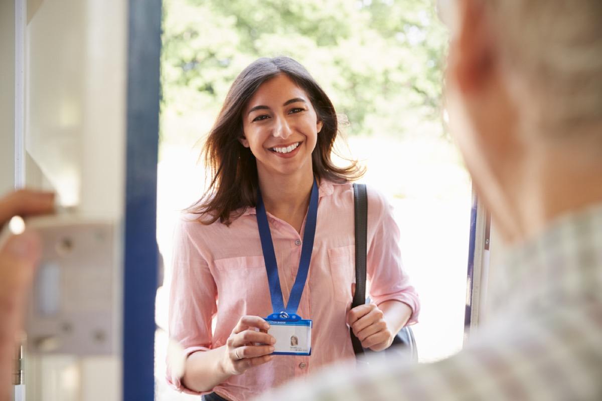 woman showing id to elderly man opening door