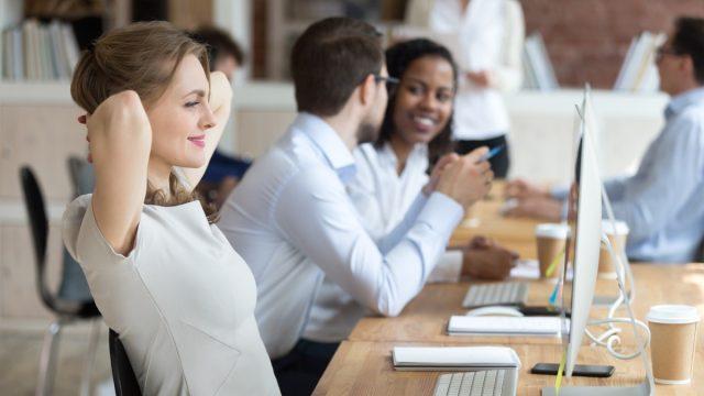 Woman smiling at her desk at work mental health awareness