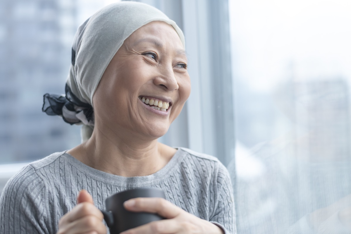 A Korean senior woman with cancer is wearing a scarf on her head. She is standing and holding a cup of tea. The woman leans against a window and smiles with gratitude and hope.