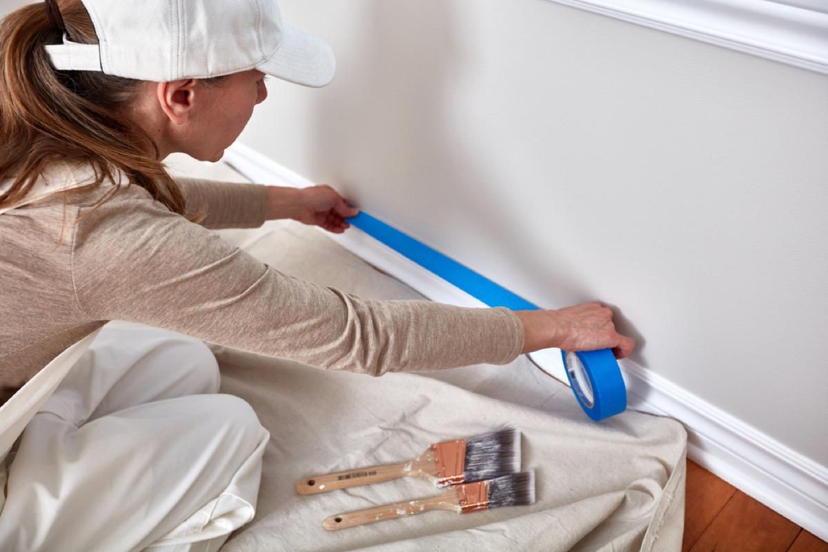 woman taping baseboard molding