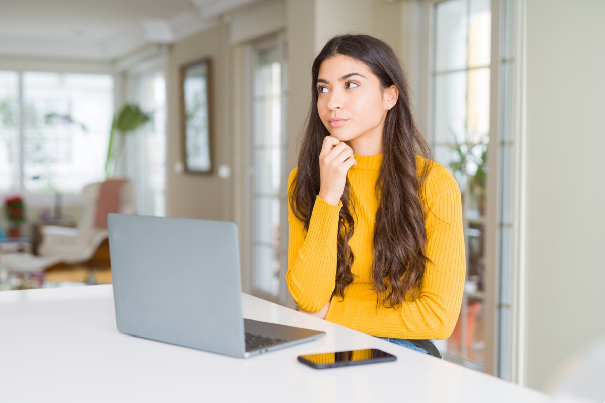 Young woman using computer laptop with hand on chin thinking about question, pensive expression. Smiling with thoughtful face. Doubt concept.