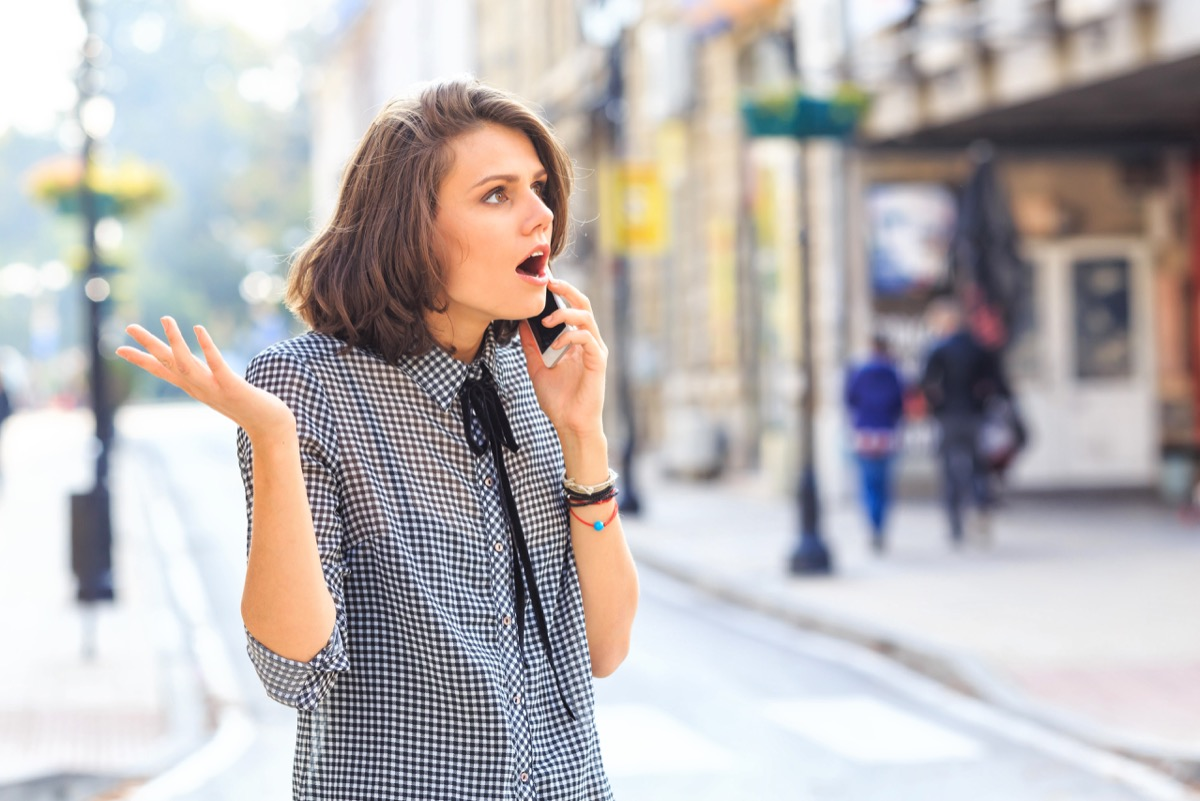 Angry woman talking on smart phone on street. Wears casual clothes.