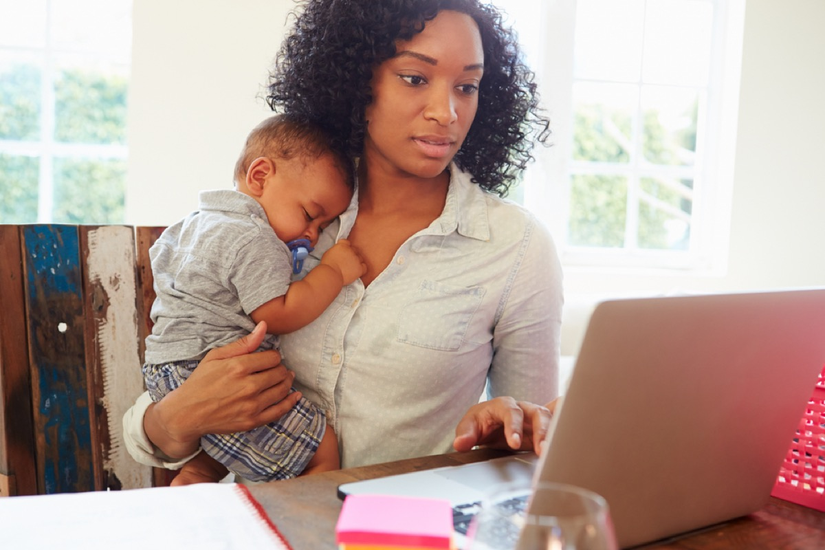 black woman holding sleeping baby while typing on laptop