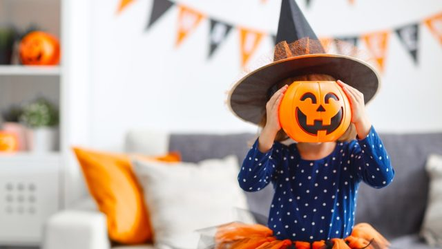 young child laughing at halloween jokes and puns