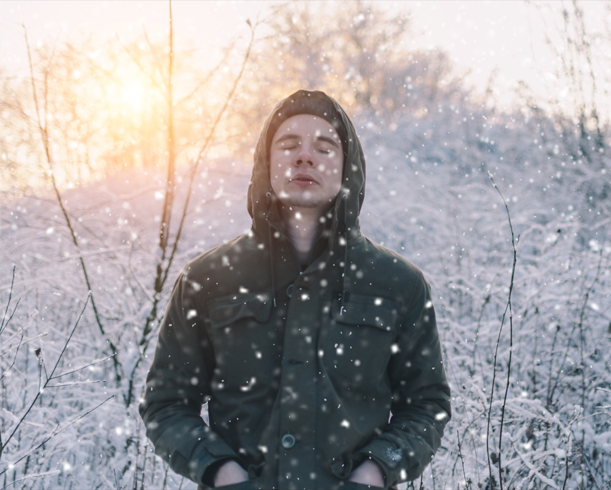 young man standing with his eyes closed in the snow
