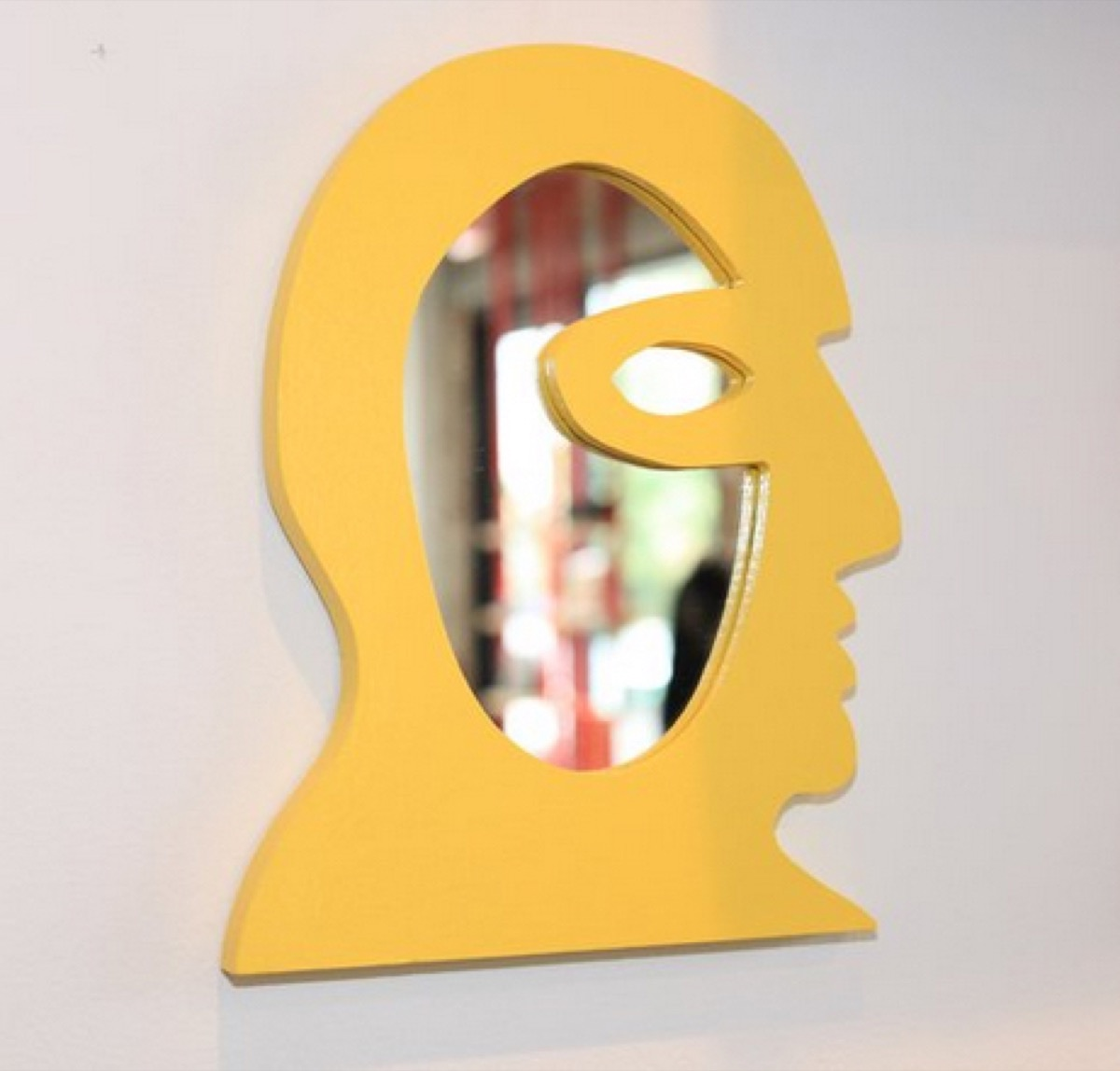 yellow mirror in the shape of a man's face