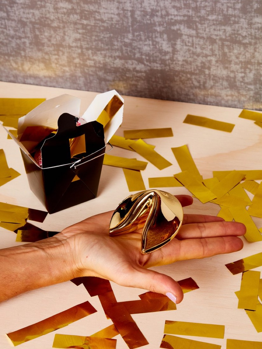 white hand holding gold fortune cookie with black takeout box and gold confetti in background