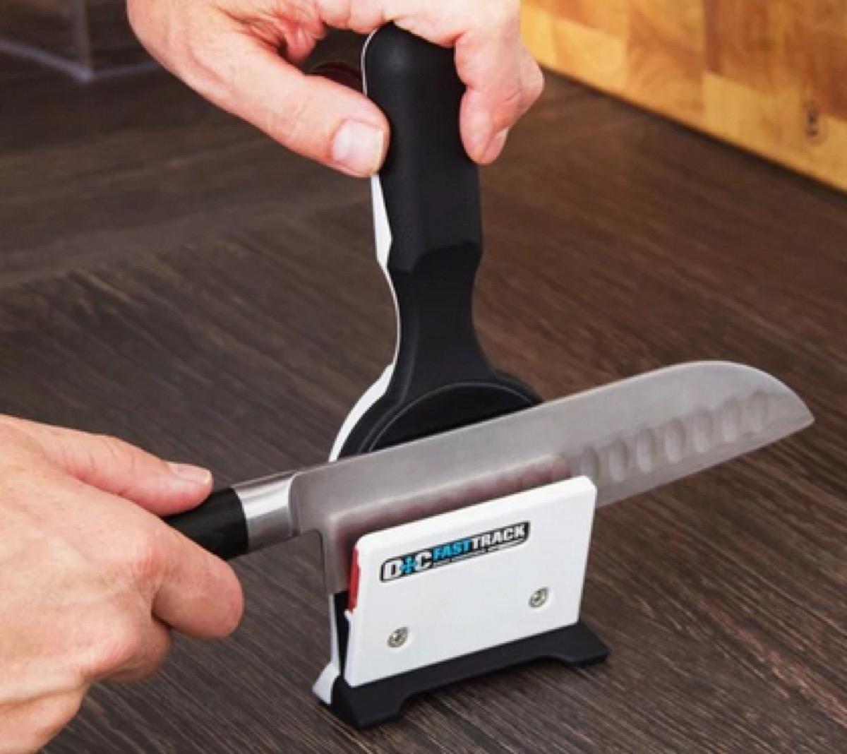 white male hand sharpening large knife