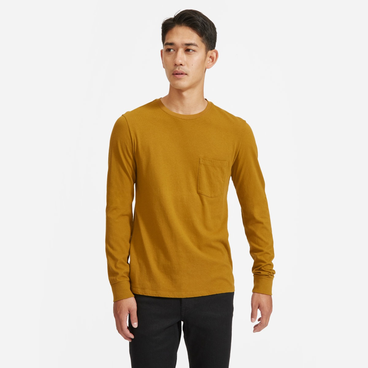 young asian man in yellow long sleeved tee and black pants