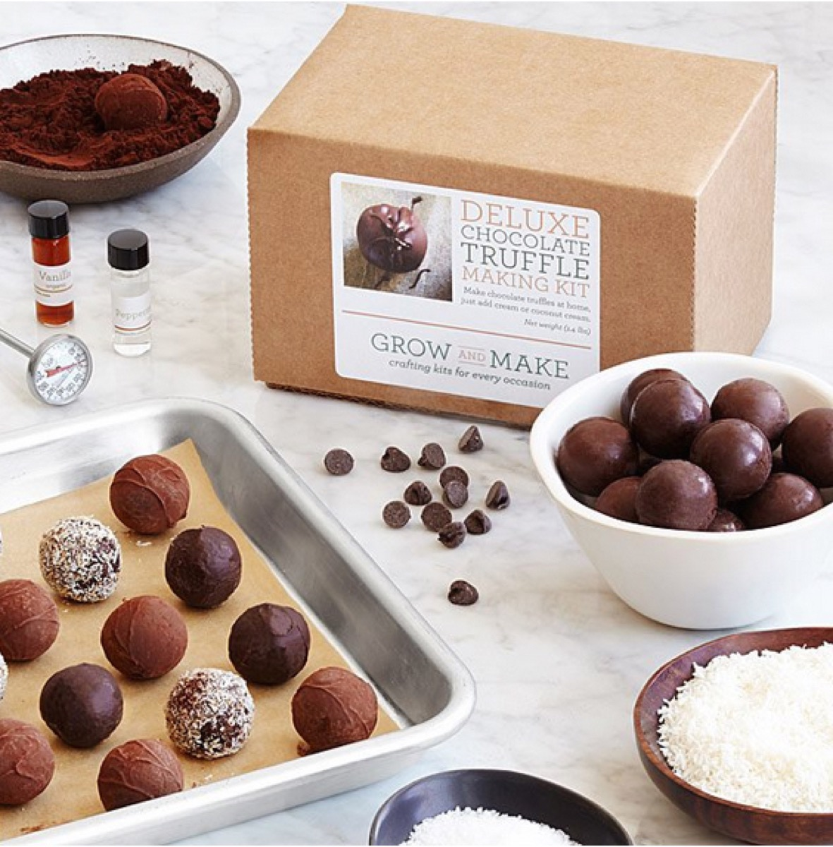 pan of chocolate truffles next to a white bowl of truffles and brown cardboard box