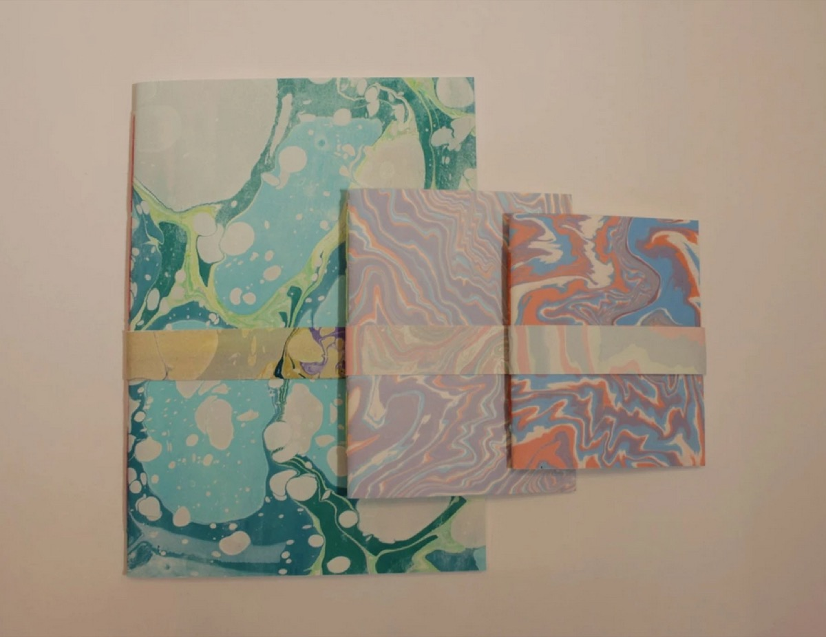 set of three notebooks with colorful marbled covers