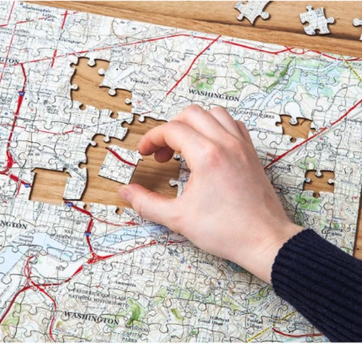 white hand putting together puzzle of washington state