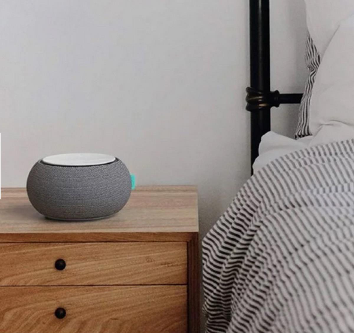 gray white noise machine on wooden nightstand next to bed with seersucker comforter