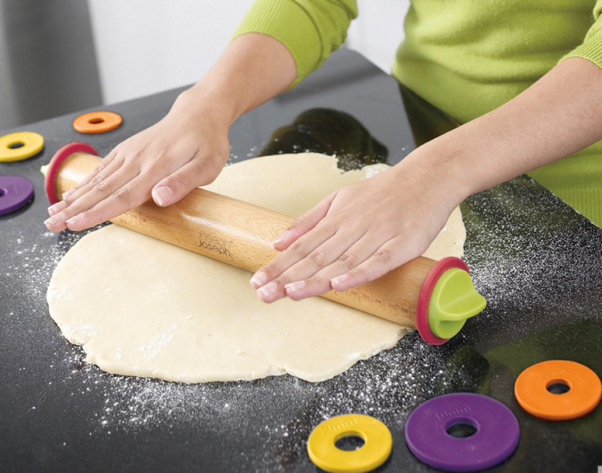 white hands rolling out dough with wooden rolling pin