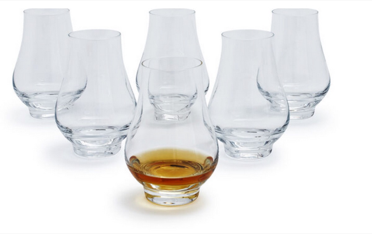 set of six clear glasses, one with whiskey in it