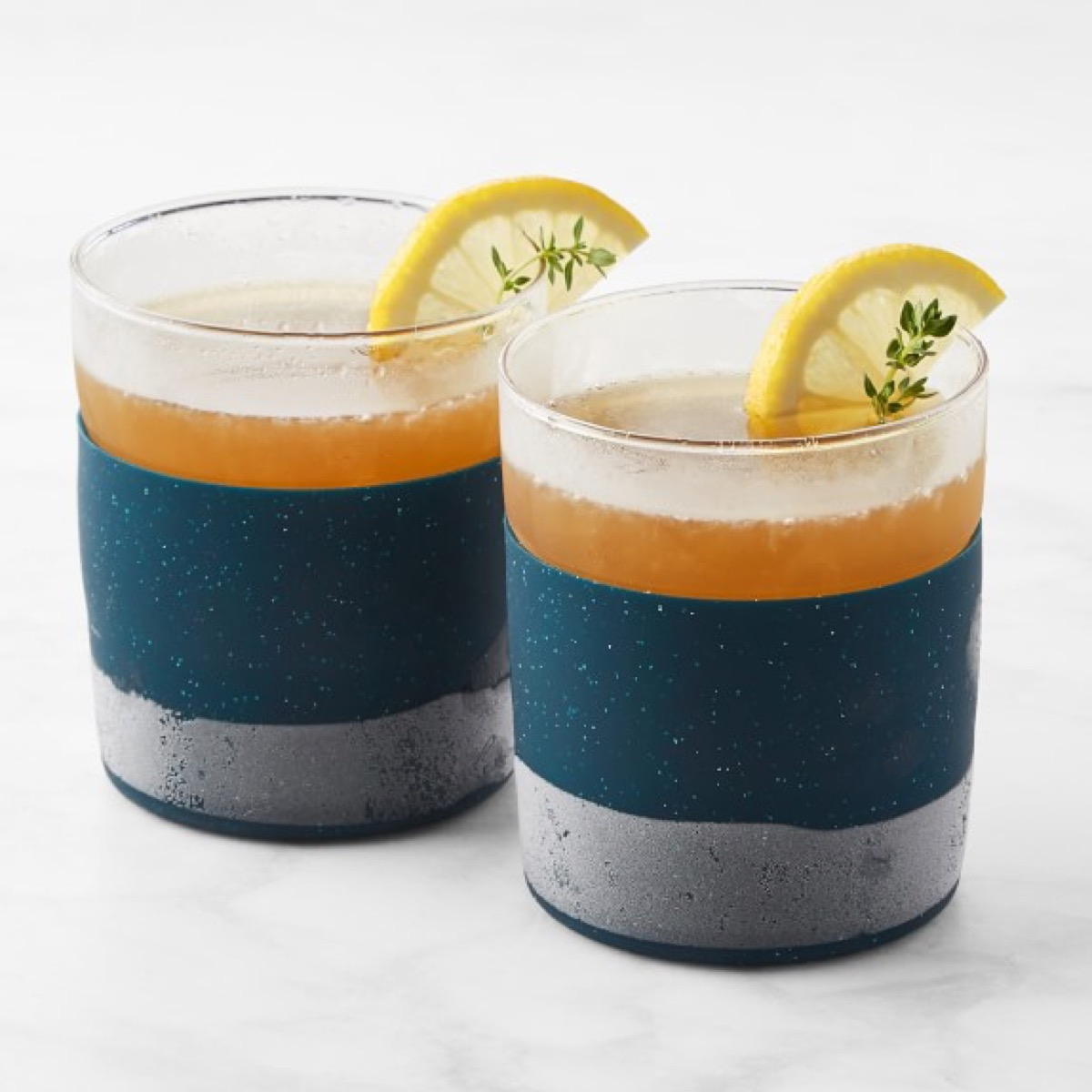 set of two colorblocked tumblers with drinks in them and lemon wedges on the edge