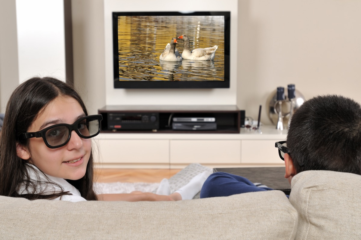 two kids watching 3D televisions together