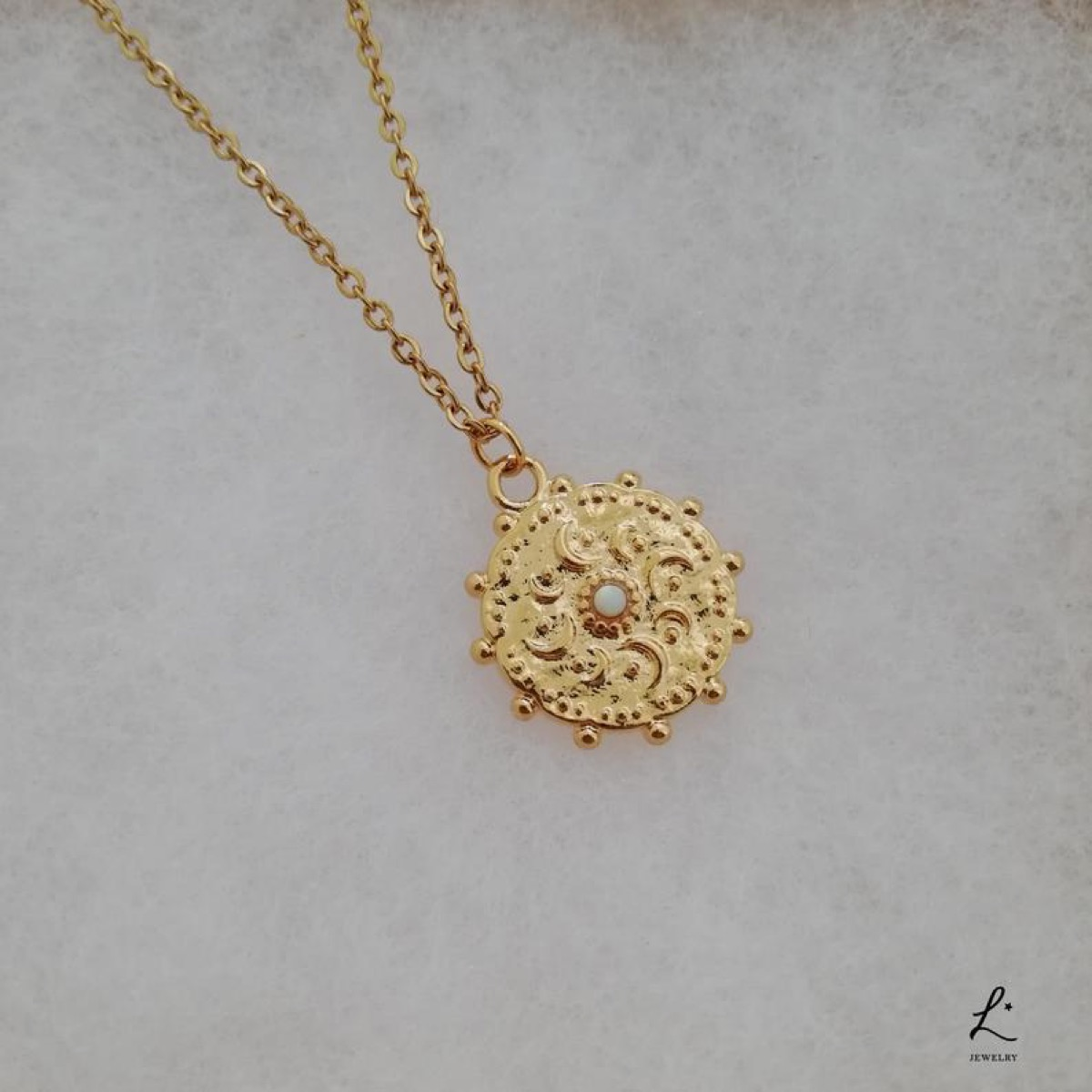 circular gold necklace on gold chain with opal center