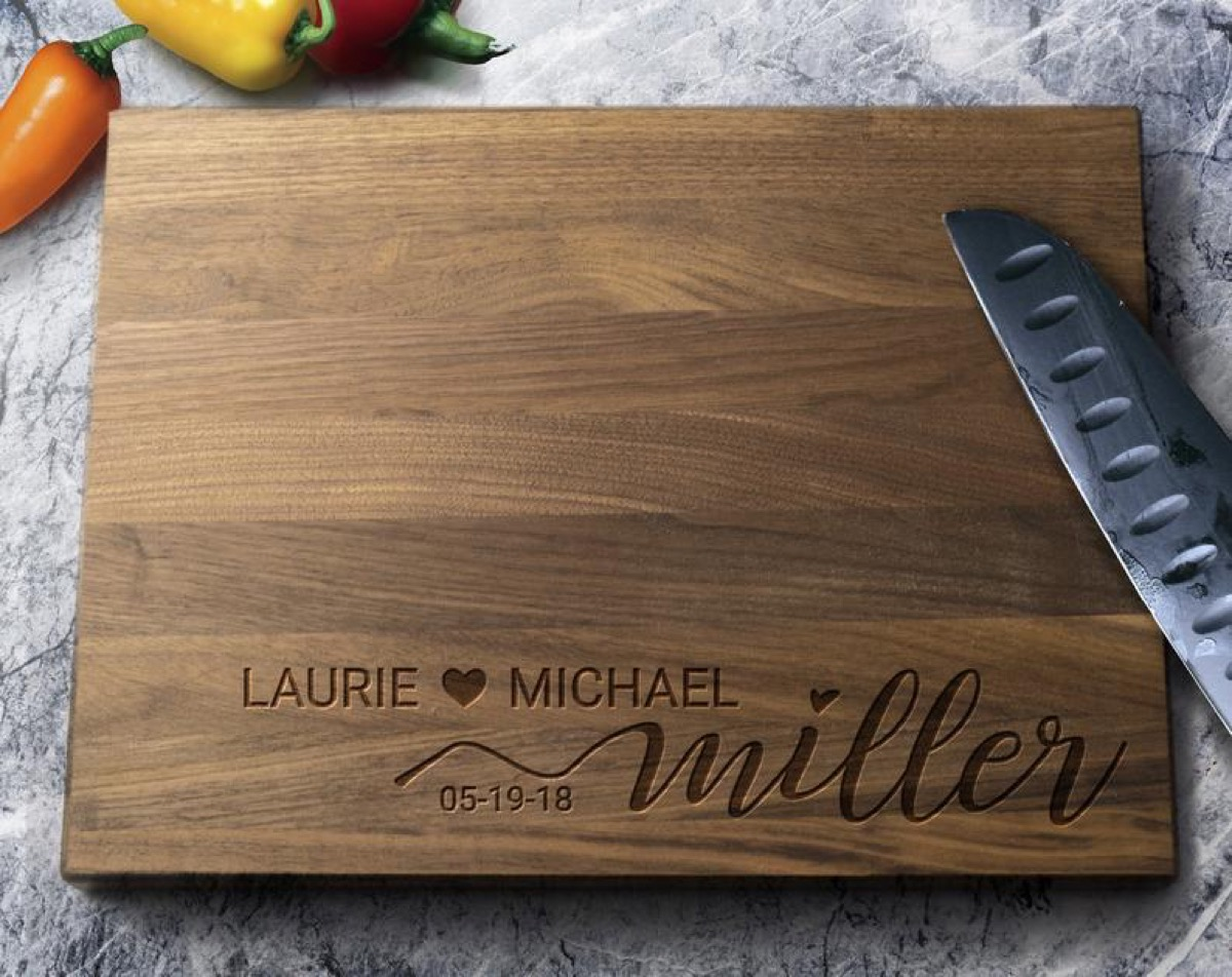 """wooden cutting board with """"laurie loves michael miller"""" engraved on it"""