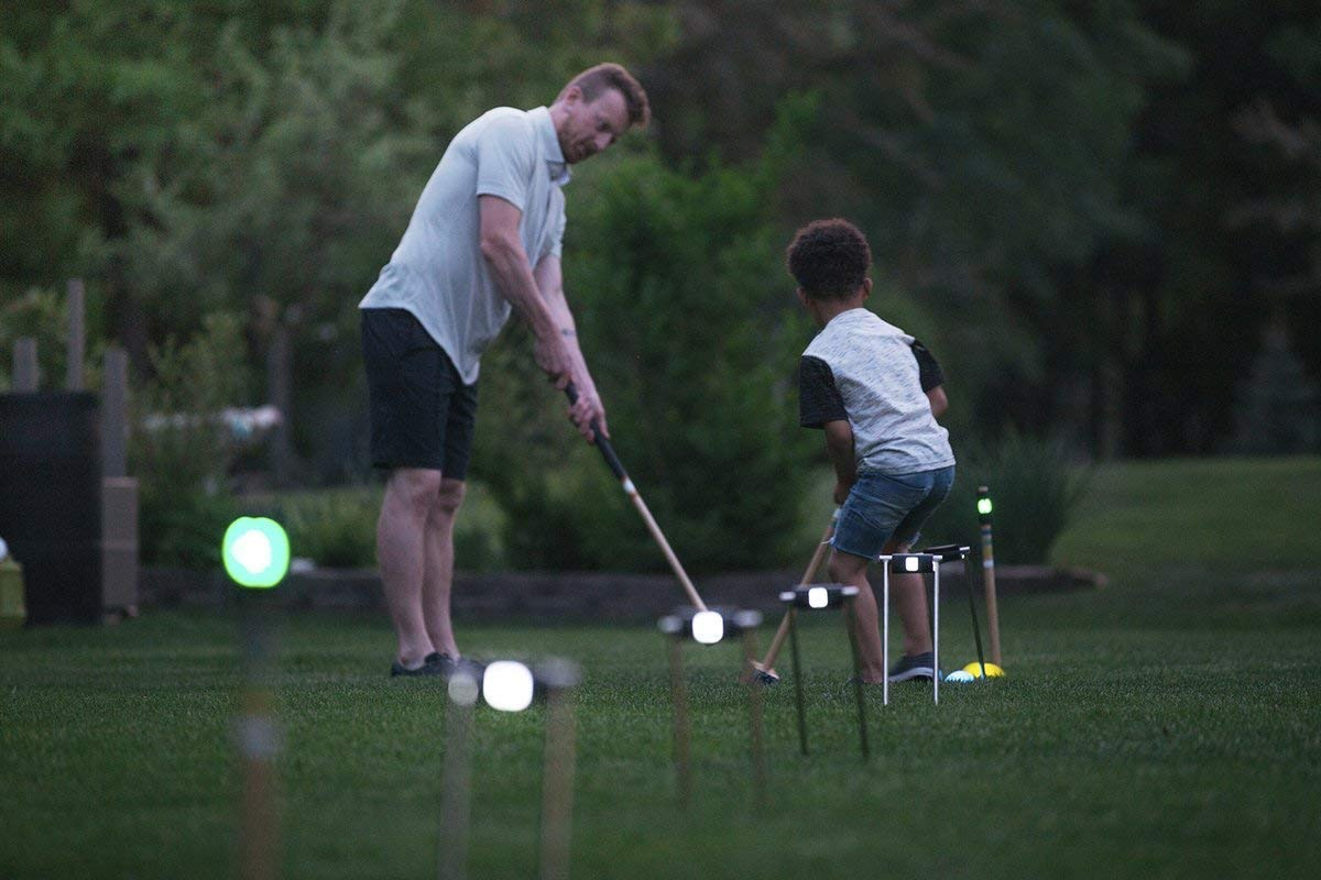man and son playing light up lawn games