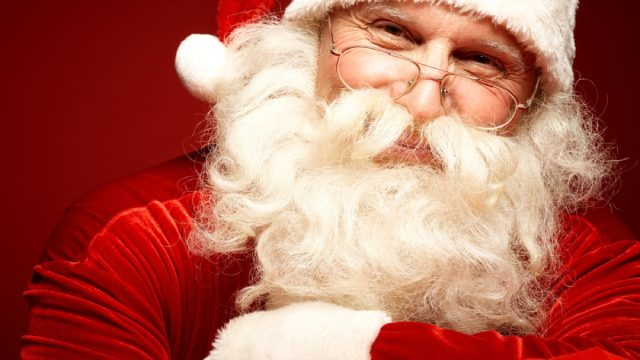 closeup of santa clause with white beard, small glasses, in red and white suit