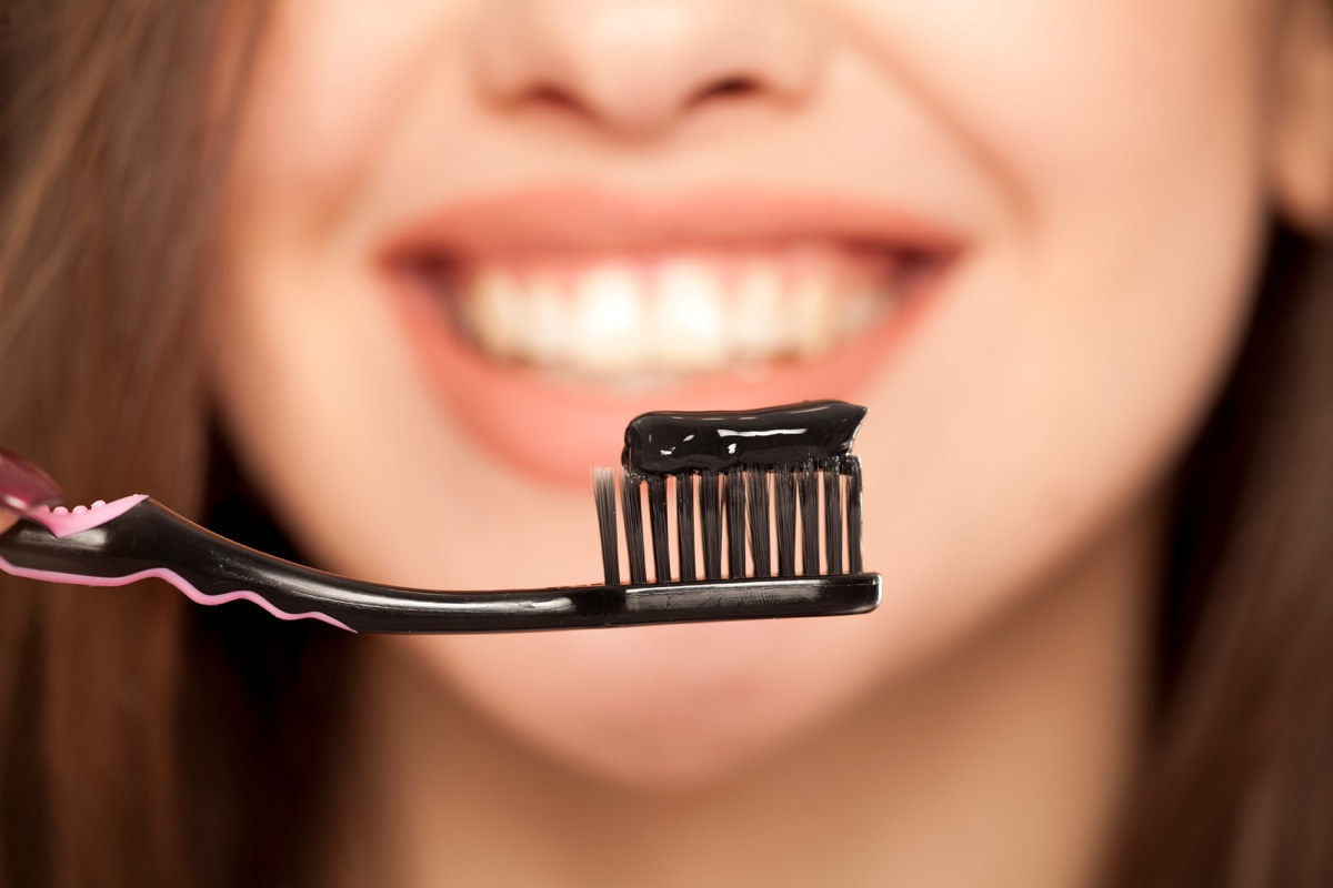 Woman brushing her teeth with activated charcoal