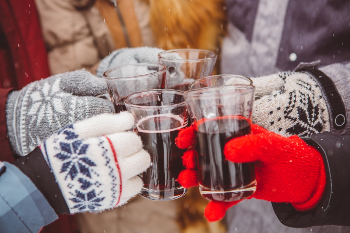 a group of friends in winter gloves tapping alcohol glasses in cheers