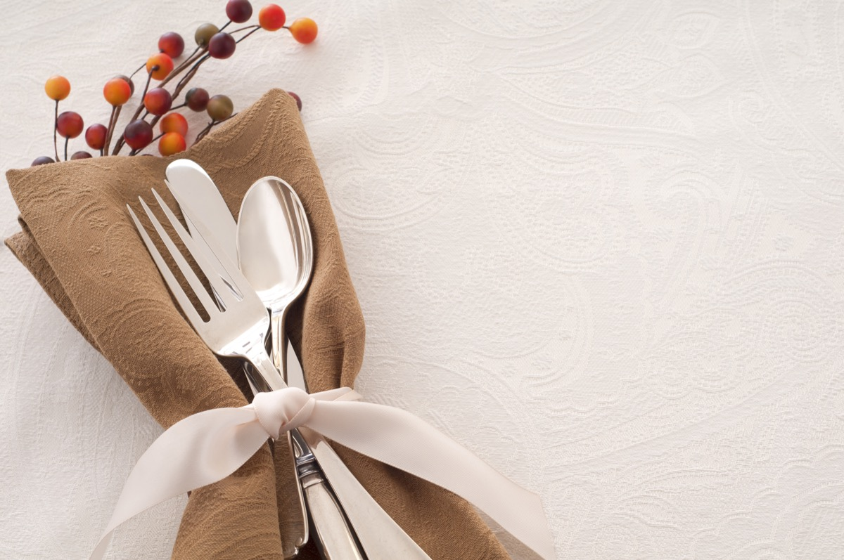 Antique Silverware Place Setting in a Brown Napkin and Tied with Ribbon on White Backgroun